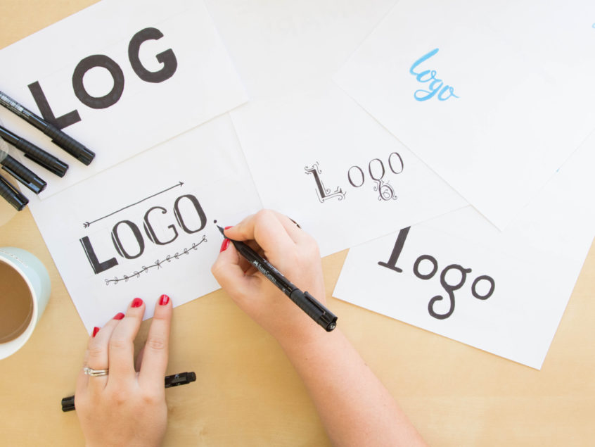 Person designing logos in different fonts.