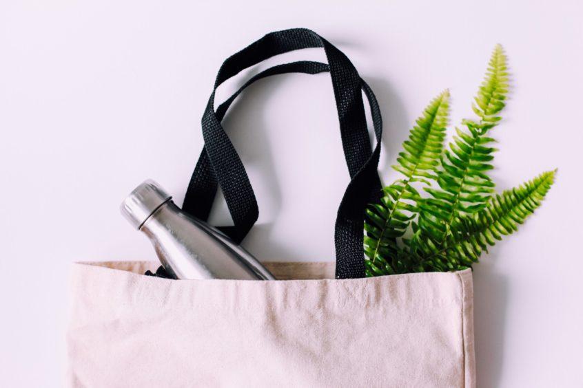 Flat lay of a reusable bag and reusable metal water bottle.